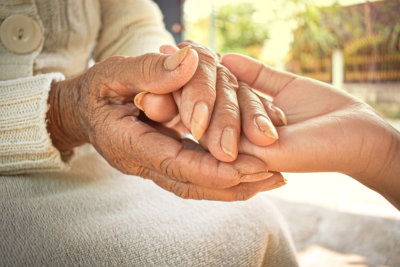 Hands of the old woman and the young woman are close to each other