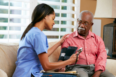 young lady checking the blood pressure of the old man
