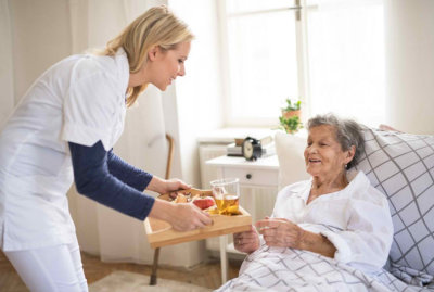 Ayoung health visitor bringing breakfast to a sick senior women lying in bed at home