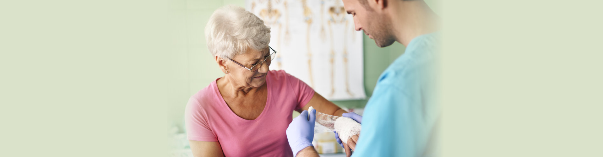 caregiver applying wound wrapping on the elder lady